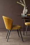 Side lifestyle image of the Golden Ochre Deco Velvet Dining Chair with dark brown wall background and dark wooden flooring with dining table in background