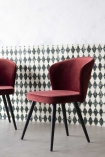 Side lifestyle image of the Merlot Red Deco Velvet Dining Chair with patterned wallpaper background and pale flooring
