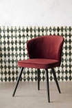 Angled lifestyle image of the Merlot Red Deco Velvet Dining Chair with patterned wallpaper background and pale flooring