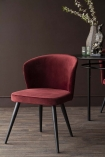 Lifestyle image of the Merlot Red Deco Velvet Dining Chair on a dark brown wall background and dark wooden flooring