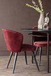 Lifestyle image of the Merlot Red Deco Velvet Dining Chair at the Black Oval Dining Table with dark brown wall background and dark wooden flooring