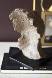 Lifestyle detail image of the back of the small Distressed Stone Effect Resting Head Ornament on pile of books and picture frame in background of marble console table with dark wall background