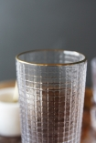 detail image of rim on Clear Glass Tumbler With Gold Rim with candle in background and grey wall