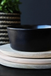 detail image of Faria Black Bowl on top of stacked white plates with striped basket in background