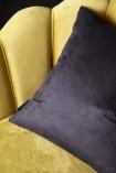 detail Image of the black back of the Summer Flowers Velvet Cushion on ochre gold velvet chair on dark wall background