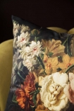 Close-up image of the Summer Flowers Velvet Cushion on ochre gold velvet chair with dark wall background