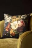 Lifestyle image of the Summer Flowers Velvet Cushion on ochre gold velvet chair with dark wall background