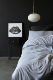 Lifestyle image of the Cruz Opal Pendant Light in a bedroom with grey bedding and lips picture frame on side table with dark wall background