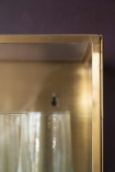 Close-up detail image of the corner of the Brass & Glass Wall-Mounted Display Cabinet on dark wall background