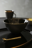lifestyle image of Glossy Noir Bowl With Gold Rim on plate with spoon and mug on black table