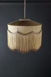 lifestyle Image of the Bespoke Inca Gold Silk Tiffany Lamp Shade with wavy fringe on dark wall background