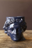 Front-on lifestyle image of the Greek Goddess Hestia Mug in blue on wooden surface and brown painted wall background