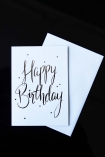 lifestyle image of Happy Birthday Greeting Card white with metallic writing with envelope on black table
