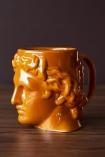 Side-on lifestyle image of the Greek Goddess Hestia Mug in Burnt Orange on dark wooden surface and dark wall background