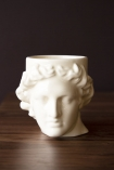 Front-on lifestyle image of the Greek Goddess Hestia Mug in white on dark wooden surface and dark wall background