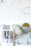 lifestyle image of Hibou Home Starry Sky Children's Wallpaper - 2 Colours Available wit white bed with blue toned bedding and cushions