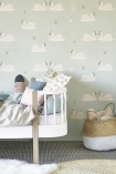 lifestyle image of Hibou Home Swans Children's Wallpaper - 2 Colours Available with white bed with blue bedding and gold and white rattan basket