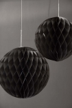 lifestyle image of Set Of 2 Honeycomb Ball Decorations - Black on dark grey wall background