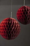 lifestyle image of Set Of 2 Honeycomb Ball Decorations - Burgundy with grey wall background
