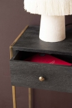 Close-up detail image of the Sophos Single Drawer Bedside Table with the drawer slightly ajar with pink velvet lamp on top and dark wall background