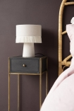 Lifestyle image of the Sophos Single Drawer Bedside Table next to a bed with a lamp on top with dark wall background