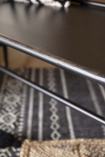 Close-up detail image view of the Industrial-Style Black Metal Two-Seater Bench with black patterned floor and rattan rug