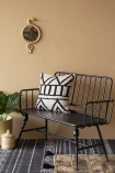 Styled lifestyle image of the Industrial-Style Black Metal Two-Seater Bench indoors on pale wall with Moroccan style cushion and black patterned floor