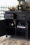 Close-up detail image view of the Industrial-Style Black Metal Drawer Storage Cabinet with open drawers with books inside and jute rug and patterned wall background