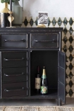 Close-up detail image of Industrial-Style Black Metal Drawer Storage Cabinet with open cabinet doors with bottles inside and patterned wall background