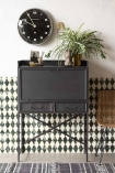 Lifestyle image of the closed Industrial-Style Bureau Sideboard Storage Cabinet & Desk with black clock and house plant on patterned wall background