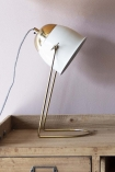 lifestyle image of White & Brass Lola Desk Lamp on wooden drawer cabinet and dusty pink wall background
