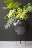 Lifestyle image of iron planter on its stand on pale flooing and with dark grey wall background