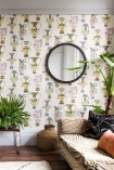 lifestyle image of Cole & Son The Ardmore Collection - Khulu Vases Wallpaper - 4 Colours Available with pale brown sofa and plants and round mirror on wall