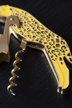 Close-up detail image of the Leopard Bottle Opener & Corkscrew on a dark surface background