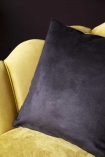 detail Image of the black back on the Two Leopards Velvet Cushion on ochre gold velvet chair with dark wall background