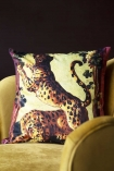 Lifestyle image of the Two Leopards Velvet Cushion on ochre gold velvet chair with dark wall background