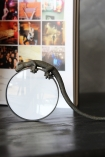 lifestyle image of Gecko Magnifying Glass on black table in front of standing open book