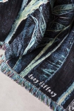 Close-up detail image of signature on Lucy Tiffney Stunning Allium Cotton Throw with pale flooring background