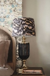 Lifestyle image of the Matthew Williamson Hyde Park Table Lamp & Animal Print Shade on side table with pale coloured and patterned wall background