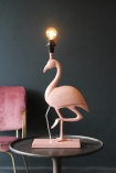 lifestyle image of Metal Coral Flamingo Table Lamp lit up on side table with pink velvet chair and grey wall backgorund