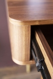 Close-up detail image of the runners on a drawer on the Mid-Century Design Two Drawer Desk with purple wall background