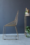 lifestyle image of side of Midas Chair with gold drinks trolley on grey flooring and dark wall background
