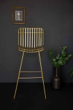 Front on angle lifestyle image of the Midas Bar Stool with plants and black flooring and copper picture frame on dark wall background