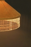 Close-up detail image of the rattan detail on the Gold Mustard Velvet & Rattan Pendant Ceiling Light when lit up on a dark wall background