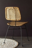 Lifestyle image of the natural Modern Woven Rattan Dining Chair facing backwards on mandala rug and wooden flooring with dark wall background