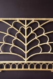 Close-up detail image of the Bloom Natural Rattan Headboard - Double Bed pattern on dark wall background