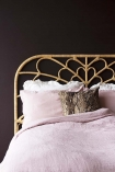 Close-up detail lifestyle of the Bloom Natural Rattan Headboard - Double Bed with pink bedding and dark wall background