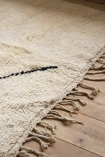 Close-up image of the tassels on the Original Moroccan Berber Large Rug on pale wooden floor