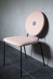 Lifestyle image of the Modern Round Back Dining Chair In Blush Pink up against a wall
