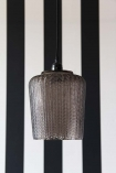 lifestyle image of Martina Smoked Glass Pendant Light with black and white striped wall background